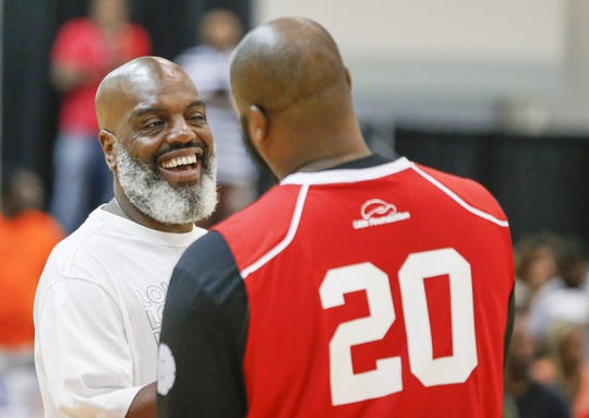 """Kevin """"Coach K"""" Lee shares a laugh with former Indiana Pacer Fred Jones before the 2018 Indiana Black Expo Summer Celebration celebrity basketball game."""
