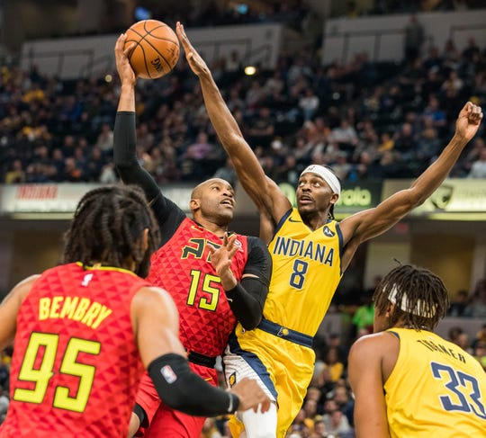 Atlanta Hawks guard Vince Carter (15) shoots the ball while Indiana Pacers forward Justin Holiday (8) defends in the first quarter at Bankers Life Fieldhouse.