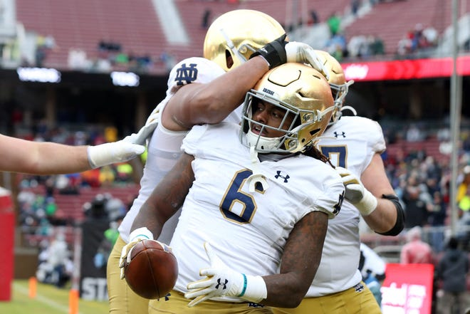 Nov 30, 2019; Stanford, CA, USA; Notre Dame Fighting Irish running back Tony Jones Jr. (6) is congratulates by offensive lineman Aaron Banks (69) after scoring a touchdown during the first quarter against the Stanford Cardinal at Stanford Stadium.