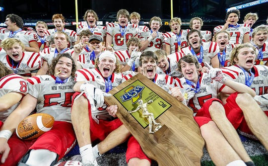 New Palestine Dragons yells after presented the state trophy at the IHSAA Class 5A state finals at Lucas Oil Stadium, Friday, November 29, 2019. New Palestine Dragons has an undefeated season beating Valparaiso Vikings in the state finals, 27-20.