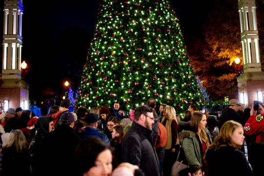 Visitors pass by the Christmas tree at the annual Regal Celebration of Lights in downtown Knoxville, Tenn. on Friday, Nov. 29, 2019.