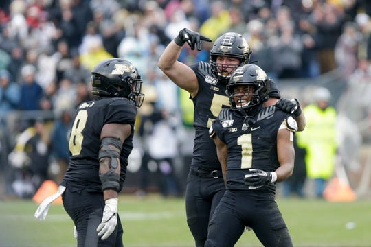 Purdue cornerback Dedrick Mackey (1) celebrates his sack with Purdue defensive end George Karlaftis (5) and Purdue defensive tackle Anthony Watts (8) during the third quarter of a NCAA football game, Saturday, Nov. 30, 2019 at Ross-Ade Stadium in West Lafayette.