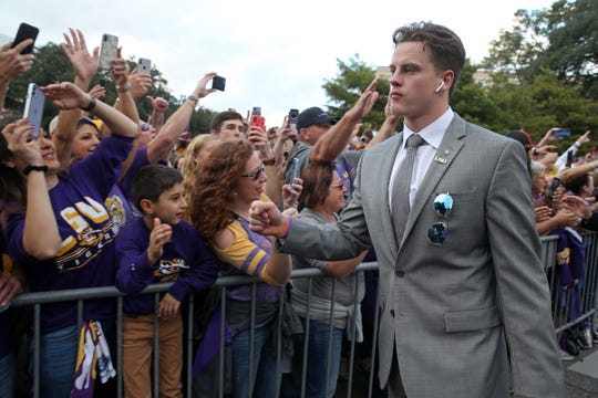 Nov 30, 2019; Baton Rouge, LA, USA; LSU Tigers quarterback Joe Burrow greets fans as he walks down Victory Hill before their game against the Texas A&M Aggies at Tiger Stadium. Mandatory Credit: Chuck Cook-USA TODAY Sports