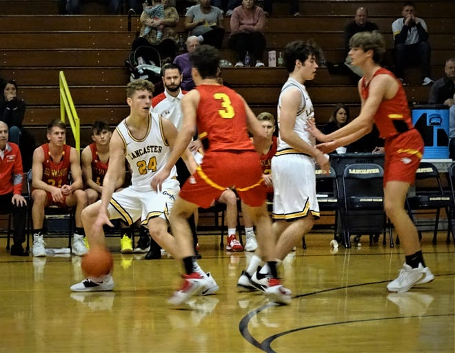 Lancaster's Jacob Davenport looks to dribble around a Big Walnut defender as Sam Finck sets a pick in the Golden Gales' 61-55 loss Friday night.