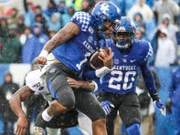 Kentucky's Lynn Bowden, Jr. leaps into the end zone to score the Cats' second touchdown against Louisville at Kroger Field on a rainy Saturday afternoon. Nov. 30, 2019