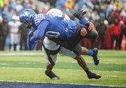 Kentucky's A.J. Rose dives into the end zone to score the Cats' first touchdown against Louisville's Isaiah Hayes.