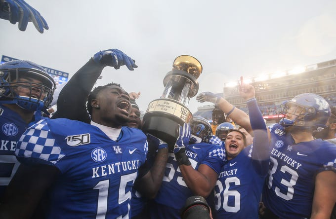 Kentucky players celebrate their convincing 45-13 win over Louisville with the Governor's Cup at Kroger Field. Nov. 30, 2019