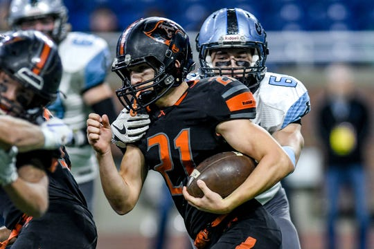 Lansing Catholic's Mason Knippen, right, tackles Almont's Mason Smith during the first quarter of the Division 5 state football championship on Saturday, Nov. 30, 2019, at Ford Field in Detroit.