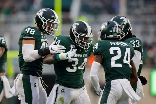Michigan State's Kenny Willekes (48), Antjuan Simmons (34), Tre Person (24) and Jeslord Boateng (33) celebrate a stop against Maryland during the first half of an NCAA college football game, Saturday, Nov. 30, 2019, in East Lansing, Mich. (AP Photo/Al Goldis)