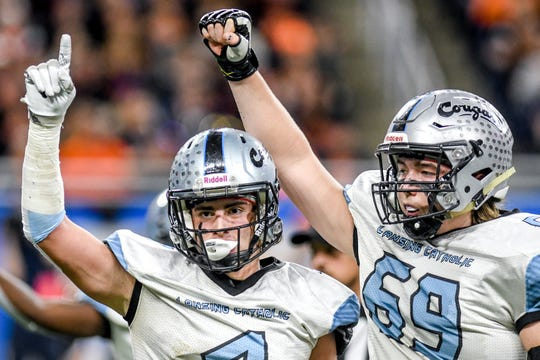 Lansing Catholic's Sam Edwards, left, and Bo Poljan celebrate after the Cougars recover an Almont fumble during the first quarter of the Division 5 state football championship on Saturday, Nov. 30, 2019, at Ford Field in Detroit.