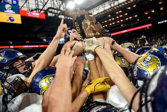 Pewamo-Westphalia celebrates with the trophy after beating Jackson Lumen Christ to win the Division 7 state football championship on Saturday, Nov. 30, 2019, at Ford Field in Detroit.