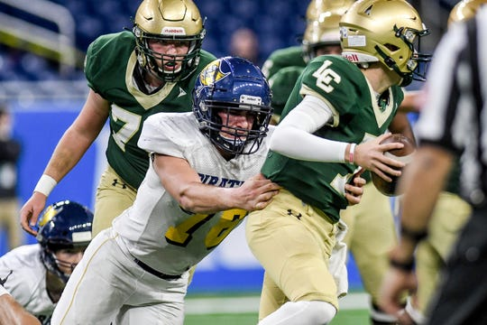 Pewamo-Westphalia's John Martin, left, tackles Jackson Lumen Christi's Brendan Wilson during the first quarter of the Division 7 state football championship on Saturday, Nov. 30, 2019, at Ford Field in Detroit.