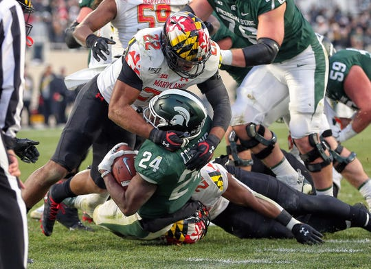 Nov 30, 2019; East Lansing, MI, USA; Michigan State Spartans running back Elijah Collins (24) is tackled at the goal line by Maryland Terrapins linebacker Isaiah Davis (22) during the first half a game at Spartan Stadium. Mandatory Credit: Mike Carter-USA TODAY Sports