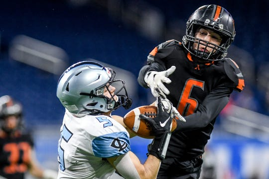 Lansing Catholic's Alex Watters, left, catches a pass as Almont's Pierce Matthews defends during the first quarter of the Division 5 state football championship on Saturday, Nov. 30, 2019, at Ford Field in Detroit.