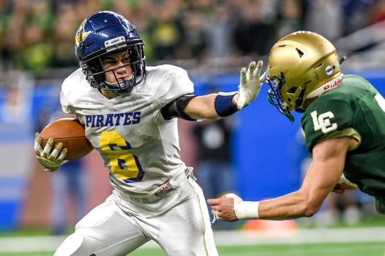 Pewamo-Westphalia's Tanner Wirth, left, stiff arms Jackson Lumen Christi's Ben Lefere on a run during the fourth quarter of the Division 7 state football championship on Saturday, Nov. 30, 2019, at Ford Field in Detroit.