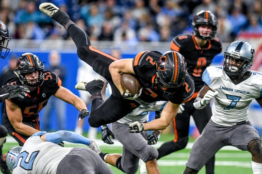 Lansing Catholic's Zach Gillespie, bottom left, upends Almont's Michael Lulgjuraj on a run during the second quarter of the Division 5 state football championship on Saturday, Nov. 30, 2019, at Ford Field in Detroit.
