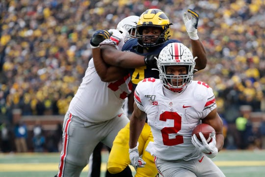 Ohio State tailback J.K. Dobbins scores one of his four TDs in Saturday's 56-27 rout of Michigan.
