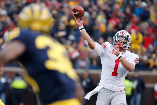 Ohio State quarterback Justin Fields threw for 302 yards and four touchdowns and survived a scary hit from his own teammate in Saturday's blowout win over Michigan.
