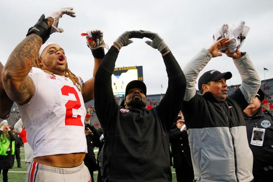 Ohio State defensive end Chase Young, linebackers coach Al Washington Jr., and head coach Ryan Day celebrate Saturday's eighth straight victory over Michigan.