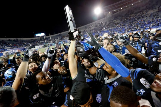 Memphis players hoist the AAC West championship trophy Friday, Nov. 29, 2019, after defeating Cincinnati 34-24 at Liberty Bowl Memorial Stadium in Memphis.