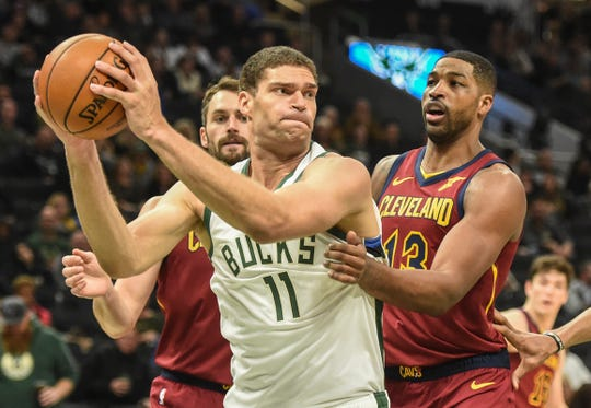Bucks center Brook Lopez looks to pass while being doubled by Cleveland's Tristan Thompson and Kevin Love.