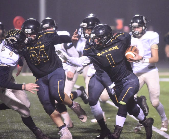 Salem's Peyton Barker runs behind the block of Chance Jackson during Friday night's 38-22 win over Carlisle.