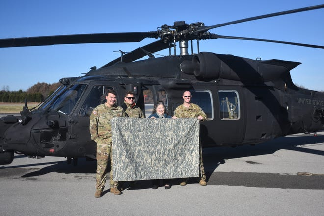 Mountain Home resident Sandra Kiphuth joins the crew of this Black Hawk helicopter in holding one of the 49 camouflaged quilts she made for for troops serving overseas. The helicopter touched down in Mountain Home on Nov. 25 to pick up the quilts.