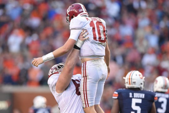Nov 30, 2019; Auburn, AL, USA; Alabama Crimson Tide offensive lineman Landon Dickerson (69) lifts quarterback Mac Jones (10) during the second quarter against the Auburn Tigers at Jordan-Hare Stadium. Mandatory Credit: John David Mercer-USA TODAY Sports