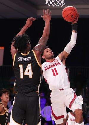 Nov 29, 2019; Nassau, BHS; Alabama Crimson Tide guard James Bolden (11) shoots as Southern Miss Golden Eagles forward Tyler Stevenson (14) defends during the first half at Imperial Arena. Mandatory Credit: Kevin Jairaj-USA TODAY Sports
