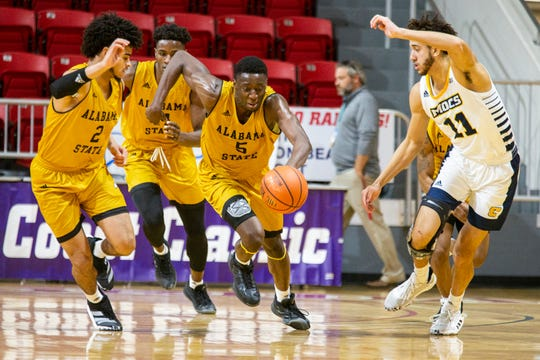 Alabama State guard Tobi Ewuosho (5), guard Kevin Holston (2) and Jeremy Hamilton (4) bring the ball up court against Chattanooga forward Rod Johnson (11) after a turnover during an NCAA college basketball game at the Emerald Coast Classic in Niceville, Fla., Friday, Nov. 29, 2019. Chattanooga defeated Alabama State 74-56. (AP Photo/Mark Wallheiser)