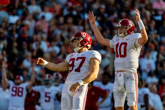 Alabama quarterback Mac Jones (10) reacts as kicker Joseph Bulovas (97) kicks a field goal against Auburn during the first half of an NCAA college football game, Saturday, Nov. 30, 2019, in Auburn, Ala. (AP Photo/Vasha Hunt)