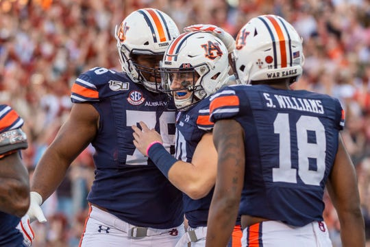 Auburn quarterback Bo Nix (10) celebrates with offensive lineman (Prince Tega Wanogho) and wide receiver Seth Williams (10) after scoring a touchdown against Alabama in the Iron Bowl on Nov. 30, 2019.