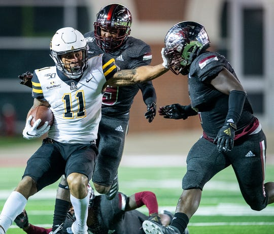 Appalachian State wide receiver Jalen Virgil (11) is stopped by Troy linebacker Carlton Martial (2) and defensive back Dell Pettus (19) in first half action on the Troy campus in Troy, Ala., on Friday, November 29, 2019.