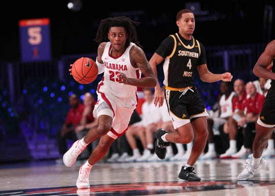 Nov 29, 2019; Nassau, BHS; Alabama Crimson Tide guard John Petty Jr. (23) dribbles past Southern Miss Golden Eagles guard David McCoy (4) during the first half at Imperial Arena. Mandatory Credit: Kevin Jairaj-USA TODAY Sports