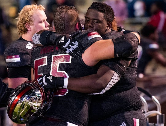 Troy offensive linemen Jake Andrews (55) and Tristan Crowder (54) hug as the clock runs out in their loss to Appalachian State in second half action on the Troy campus in Troy, Ala., on Friday, November 29, 2019.