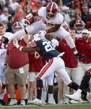 Alabama running back Najee Harris (22) hurdles Auburn defensive back Jeremiah Dinson (20) in first half action in the Iron Bowl at Jordan-Hare Stadium in Auburn, Ala., on Saturday, November 30, 2019.