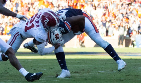 Alabama defensive back Jared Mayden (21) grabs the facemask on the helmet of Auburn running back JaTarvious Whitlow (28).