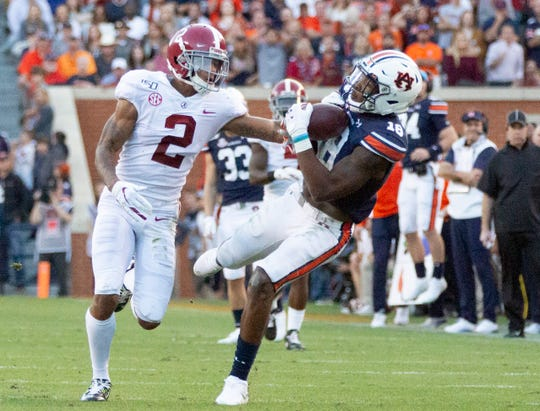 Auburn wide receiver Seth Williams (18) catches a wild pass as Alabama defensive back Patrick Surtain, II, (2) tries to block it.