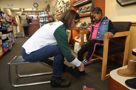 Mary Murdoch, great grand daughter of the founder of the JT Murdoch Shoe Store on Bloomfield Ave. in Bloomfield helps Ireyana Smith 4 of Belleville with a pair of boots as JT Murdoch Shoes participated in Small Business Saturday on November 30, 2019.