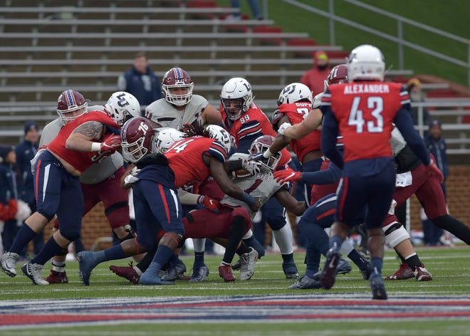 Liberty players take down New Mexico State's Jason Huntley during an NCAA college football game  in Lynchburg, Va., on  Saturday.