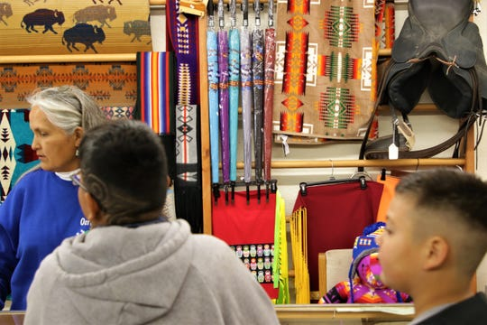 Cashier at Alex Benally's Hogan Eletta Zmudzinski helps customers Ethan Begay, left, and Jerimiah Tracy, right, look for gifts on Nov. 30, 2019, Small Business Saturday in Farmington.