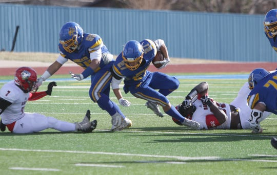 Bloomfield's JT Seitzinger tries to stay on his feet against Portales during Saturday's 4A state football championship game at Bobcat Stadium in Bloomfield.