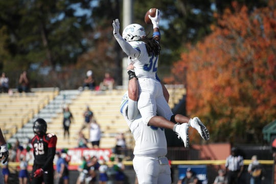 Anthony Johnson Jr. is hoisted up after scoring one of his three touchdowns in Saturday's thrilling win for UWF at Valdosta State in the second round of the NCAA Division II  playoffs.