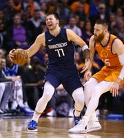 Mavericks forward Luka Doncic reacts after getting fouled by Suns center Aron Baynes during a game Nov. 29.