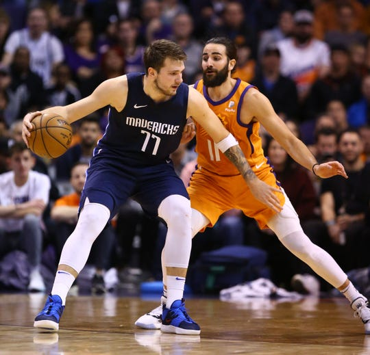 Dallas Mavericks forward Luka Doncic (77) is pressured by Phoenix Suns guard Ricky Rubio (11) in the second half on Nov. 29, 2019 in Phoenix, Ariz.