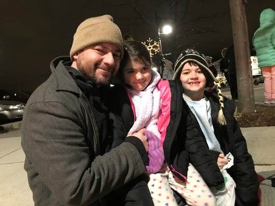 Randy Willis waits with his daughter Kaydence, 5, and son Carson, 8, at the intersection of Military and Wall streets for the 2019 Sperry's Santa Claus Parade Friday, Nov. 29, 2019, in downtown Port Huron.
