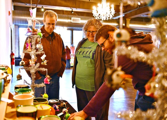 From left, Scott Mann, Bonnie DeBold and their son Sean Mann, all of York Township, look at Creature Clayworks by Mark Broomell, of Spring Garden Township, during Merry Market at the Bond on Small Business Saturday at Royal Square in York City, Saturday, Nov. 30, 2019. Dawn J. Sagert photo