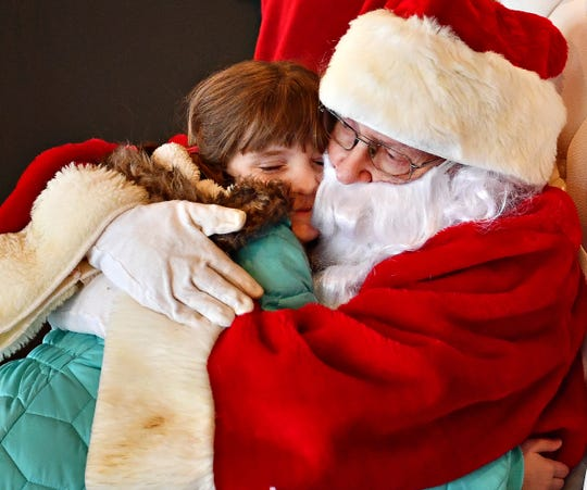 Elaine Scallorn, 8, of Springettsbury Township, hugs Santa, played by Michael Garner, of Stewartstown, during Merry Christmas at the Bond on Small Business Saturday at Royal Square in York City, Saturday, Nov. 30, 2019. Dawn J. Sagert photo