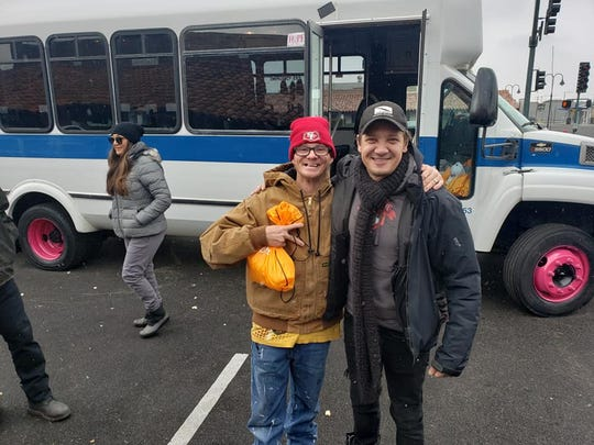 "Actor Jeremy Renner is pictured with a man who's received a ""Kindness Kit"" on Fourth Street in Reno on Thanksgiving Day 2019."