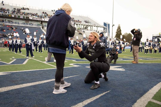 Nevada punter Quinton Conaway proposes to girlfriend Miranda Powell at midfield before Saturday's game against UNLV.